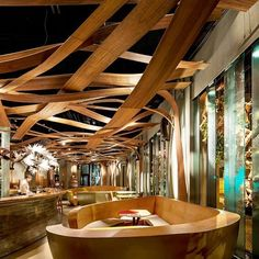 El Equipo Creativo faced one primary challenge when designing Barcelona's Ikibana #Restaurant: fusing #Japanese and #Brazilian culture together into one cohesive space. Both cultures, despite being wildly different, find common ground in a deep appreciation for the natural #environment. With this in mind, El Equipo Creativo incorporated a remarkable #wooden ceiling system that seems like a majestic forest of interlacing vines and branches. Seating areas, organized in fluid groups of bright…