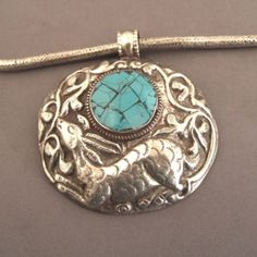 """Silver, turquoise, Nepal   Description  A charming pendant coming from Katmandou with different animal and floral motives on each side and pleasant for everyday wearring… the chain silver """"snake"""" is old and beautifull …  Weight:119,1gr    Height:Pend : 2,36 inch    Width:Pend : 2,75 inch    Length:16,9 inch    www.halter-ethnic.com   see """"My lucky finds"""""""