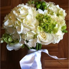 A classic, yet fresh bridal bouquet. I left space on the stem to pin the Bride's mother's brooch. Flowers: White Hydrangea, Green Mini Hydrangea, Green Hypericum Berries, White Eskimo Roses, White Dendrobium Orchids, Green Lisianthus, and White Freesia. www.andrealaynefloraldesign.com