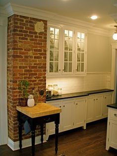 exposed brick chimney, not used; white cabinets on legs; narrow base cabinets near door; darker wood floor
