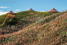 Photograph by Michael Yamashita. @yamashitaphoto A hillside covered by thousands of Tibetan prayer flags in the colors of a rainbow. A prayer flag is a cloth printed with a blessing or prayer. They are often planted on mountain ridges as Tibetans believe the wind will blow the message and disperse blessings and good fortune to all beings around the world. #Kham  #Tibet #Lhagong #Sichuan #China @natgeocreative @thephotosociety by natgeo