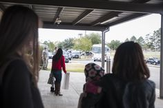 Families watch as the bus carrying their loved ones approaches during a deployment return at Moody Air Force Base, Ga., Jan. 9, 2014. This was one of many groups totaling more than 60 people who returned from Camp Bastion, Afghanistan. (U.S. Air Force photo by Senior Airman Jarrod Grammel/Released)