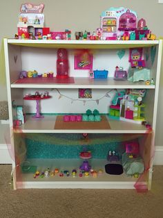 Shopkins house! Bookshelf from Walmart and added some decorations from cardstock and tule I had at home. Also cut out pictures from Shopkins boxes to hang around for decorations! Easy quick project to do with the kids! Also a great way to keep them organized