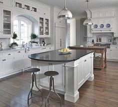 Large, white kitchen with double islands of mixed wood. Rounded bar at end of main island.
