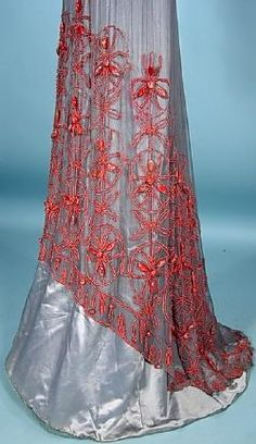 """1911 JACQUES DOUCET, Paris Elaborately Beaded Chiffon Evening Gown of wedgewood-blue/gray silk chiffon heavily embroidered in small coral and large """"white-heart"""" beads over matching blue/gray satin with matching velvet sash. Pink satin accentuates the neckline and upper back and gold metallic lace adorns the bodice front and back and inner sleeve. Detail"""