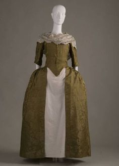 """Dress: 1770-1775, silk brocade, low square neckline and elbow-length sleeves, no accompanying underskirt. """"Worn by great-great-great-great grandmother of donor [Mrs. George B. Nelson] in her wedding. The homespun linen lining of this gown was taken and scraped into lint and used for dressing wounds of the American Revolutionary War soldiers in the year 1776. (Transcribed from information sewn onto dress.)"""""""
