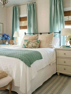 Inexpensive home decorating... yet another great example of using high-hung curtains to make windows appear larger. Love how the curtains match the bed, too!