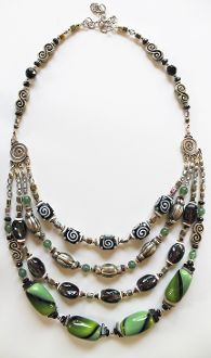 A four-strand necklace with silver accents. There are lots of squiggles and swirls to keep the circle theme going. Here we have a palette of greens and deep purple. In spite of all that this piece is composed of I think it comes off as very understated and elegant. It's a traditional piece that can be worn with anything.