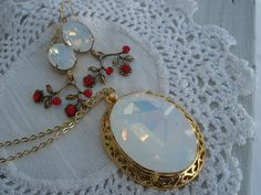 This is a beautiful pendant necklace and matching earrings made with vintage new Swarovski faceted white opal glass jewels in gold settings.  The
