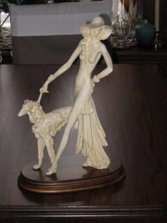 """ELEGANT ART DECO SCULPTURE (REPLICA) BY A. SANTINI. IT IS ONE OF THE MANY FAMOUS REPLICA SCULPTURES BY THIS ARTIST. IT HAS A STAINED AND VARNISHED WOODEN BASE, WITH A SANTINI CARVED INTO THE BOTTOM RIGHT HAND CORNER OF THE SCULPTURE. THE WOMAN IN THE SCULPTURE IS WALKING A RUSSIAN WOLFHOUND (BORZOI) ON A LEASH, AND IT MEASURES 17 1/2"""" TALL x 11"""" LONG x 5"""" WIDE. 75."""