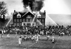 Spectators divide their attention as the Mount Hermon High School football team in Massachusetts hosts Deerfield Academy during a structure fire in the Mount Hermon science building on November 24, 1965. The science building was destroyed, and Mount Hermon lost the football game, ending a two-year-long winning streak. (AP)