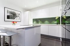 High gloss kitchen with white lacquer kitchen island and seating. This design includes metallic Anthracite wall units, a vibrant green splashback, and a Compac Carrara Quartz worktop.