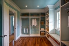 HGTV.com showcases the HGTV Dream Home 2015 master closet, featuring coastal blue walls combined with stately white crown molding and custom storage units delivering a luxurious finish.