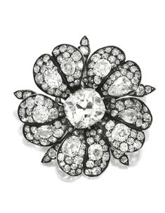 SILVER-TOPPED GOLD AND DIAMOND BROOCH. Designed as a flowerhead centered by an old mine-cut diamond, the petals centered by four antique pear-shaped diamonds and six old mine-cut diamonds, further accented with numerous smaller old mine-cut diamonds, late 19th century.