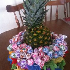 A styrofoam ring wrapped in a lei with a pineapple in the middle. Then I poked 2 bags of dum dums in the ring! Tada! Made this for my daughters luau bday party! The kids loved it & so did the adults! Great for a centerpiece. :-)