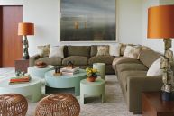 The media room consists of a sprawling sectional sofa covered in an indoor-outdoor linen by Ann Kirk, crucial for family time wear and tear. Five custom Siglo Moderno tables in minty blue-green float next to a pair of Paul Evans Brutalist lamps.