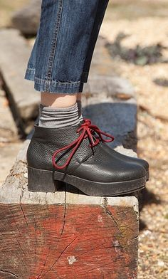Lace-up platform ankle boots made from soft black pebbled leather with striking red laces.