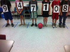 I made a set of numbers 0-9, laminated them, and attached a string from end to end. I then taped off a place value chart on my floor that in...