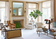 Antique sconces flank a mirror that conceals a flat-panel TV in this gorgeous living space. - Traditional Home ®/ Photo: Werner Straube / Design: Skip Sroka