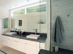 This sleek gray and white bathroom features a glass-enclosed shower and a double-sink, floating vanity. Transom windows above the mirror lend natural light to the space.