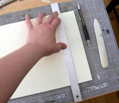 """For this step you will need the inner paper, the almost completed book cover, the cutting mat, pencil, craft knife, permanent adhesive and folding bone.   Overlay the inner paper onto the nearly finished book cover. Position so it is about 1/8"""" away from the outer edge. Mark out and trim any excess paper using the pencil, ruler and craft knife (picture 1). Retain these scraps for later.   Spray the inner paper with the spray adhesive"""