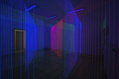 Korean artist Jeongmoon Choi creates installations that look like glowing geometric drawings but are actually composed of colored threads that are illuminated by UV light.