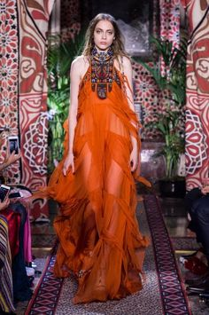 La modella indossa un abito arancione trasparente a balze e strati, con ricami ispirati ai nativi americani.