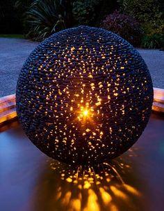 Planeta întunecată contemporană sferică strălucitoare artă grădină noaptea. Acest lucru, sferă de grădină tactilă netedă din pietre puddle lustruite este transformat după întuneric printr-o lumină interioară subtilă.