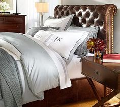 Grey bedding on brown leather headboard and grey walls.