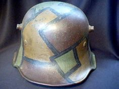 """Rare 1918 model German helmet with ear cut out. The main purpose of the cutout helmet was to provide better hearing in the trenches and to reduce explosive resonance and echo created by the large flared skirt. A correct M18 """"cut-out"""" helmet must bear the maker mark ET 64. The Eisenhutten werk plant at Thale was the only company to receive a contract to produce this helmet. They made this helmet only in shell size 64 and less than 100,000 were produced."""