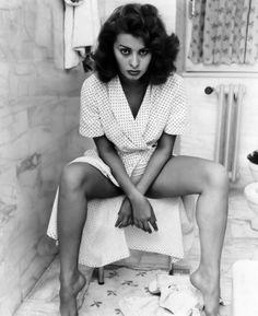 Sofia Loren sitting in bath room.