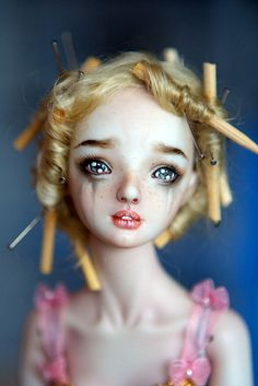 This is fantastic art.  Porcelain doll, measures a few inches, toothpicks and pins in her hair.  Makes me want to cry it is so sad and beautiful. and creepy