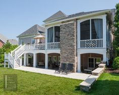 Two story double porch with outdoor fireplace, travertine patio, and AZEK deck contemporary exterior