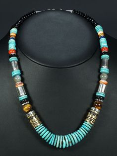 The drum beads suggest this was made by Navajo Tommy Singer or one of his family.  turquoise