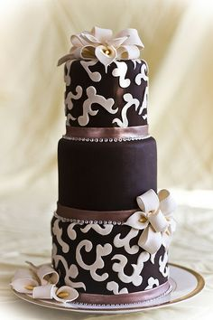 Chic, classic, and elegant modern wedding cake featuring intricate fondant work and beading with ribbons in a palette of ivory, silver and brown.