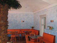 Restaurant mit orangener Einrichtung und hellblauer Wand. Spritztechnik durch die Malerwerkstätte Manfred Hübl in Annweiler (76855) | Maler.org