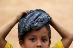 A boy covers his head with a glove during a baseball practice in the coastal town of Ocumare, February 25, 2011.  REUTERS/Jorge Silva