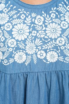 Nothing says cute and comfy like the Mary Jane Embroidered Blue Chambray Dress! Breezy woven fabric forms a sleeveless smock dress with ivory floral embroidery and a full skirt. Raw, back-stitched hems.