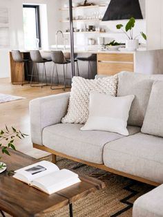 A live-edge wood & steel coffee table, chunky knit pillows and the handloomed jute & wool Serac Rug boost the material mix.