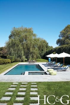 Hampton Home. Bluestone frames the pool area, which is decked out with Janus et Cie chaise longues and umbrellas.