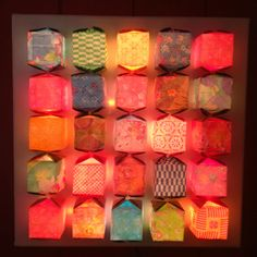 Origami cubes on string lights mounted on12X12 canvas.