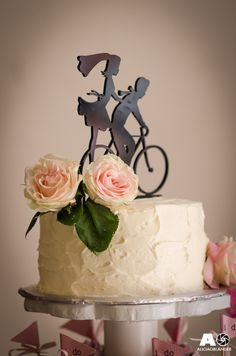 Bicycle themed wedding featuring a bike cake topper and lots of cupcakes with a light pink color palette.