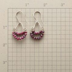 """Faceted rubies flash an ear-to-ear grin, delivering happiness wherever they happen to be. Sterling silver; French wires. Handcrafted in USA exclusively for us. 1-7/8""""L."""