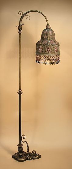Custom 'BELL' shade on ornate, asymmetrical-base, bridge lamp. was constructed to fit the beaded fabric exactly. This piece was a section of an extraordinary, 1910's evening gown, made from cut-out and embroidered gold and silver lamp, bejeweled with glass jewels and sequins and over-embroidered with pink, and black satin glass beads. Hand beaded fringe reflects the colors of the the shade. http://www.antiqueartistry.com/floorlamps/