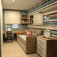 Quarto com papel de parede azul listrado, bicama lateral, cômoda e bancada de escritorio.