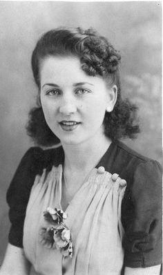 I love everything about this pretty young 1940s woman's look, from her curled bangs to the charming floral corsage on her dress. Reminds me of my beautiful mom back then!