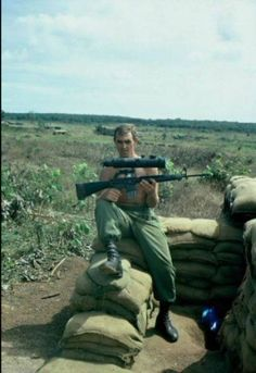 Vietnam War - an Australian soldier holds up an M16 with attached starlight scope.