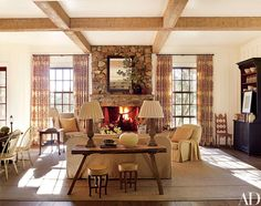 The family room is highlighted by whitewashed cypress beams and a fireplace made of local stone; the club chair at right is by Suzanne Kasler for Hickory Chair, the antique painted cabinet is from Ainsworth-Noah, and the curtains are of a Robert Kime fabric.