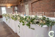 Winter top table flowers with trailing ivy and fairy lights - Owen House Barn - Laurel Weddings