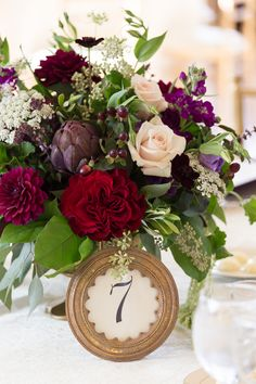 The centerpieces featured blush roses, ruby dahlias, red garden roses, purple stock, Queen Anne's lace, artichokes, and seeded eucalyptus.   Photo by Cavin Elizabeth Photography, Venue: Morais Vineyards and Winery, Flowers: Petals by the Shore